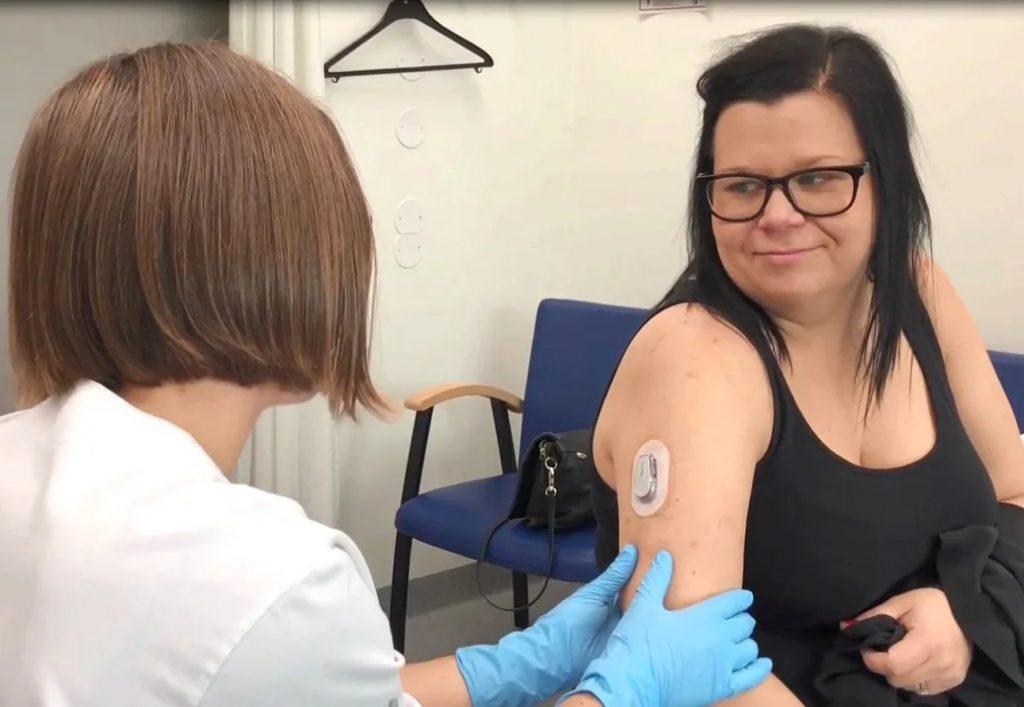 På bilden ses hur en kvinna, här läkaren Josefin Ulriksdotter, undersöker en patient som har en glukossensor fastsatt på högra överarmen.