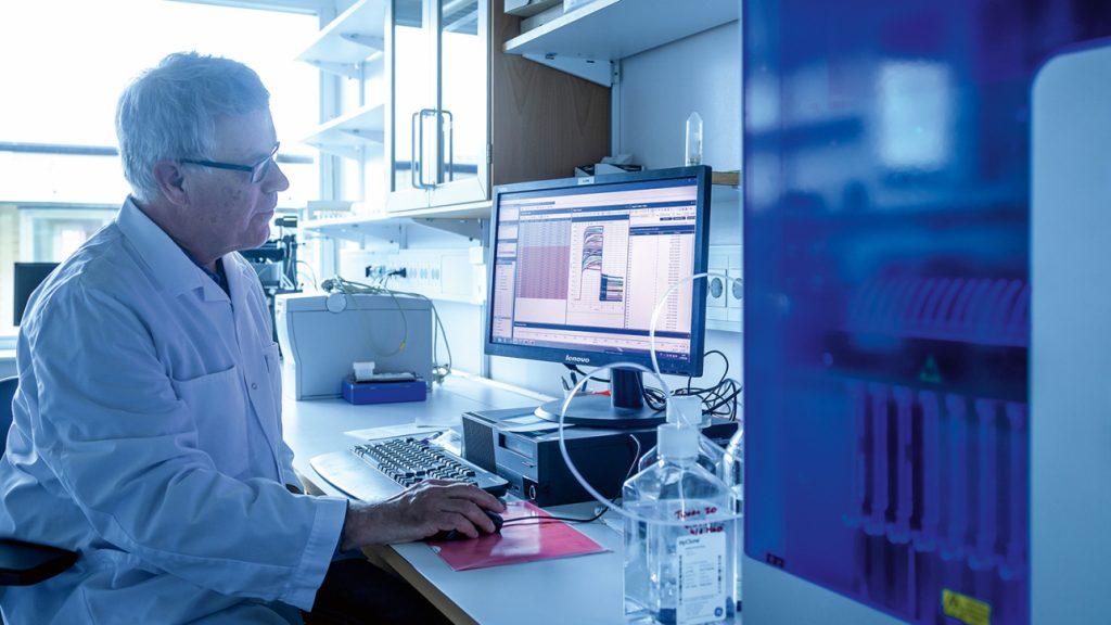 På bilden ses Mats Ohlin, iklädd vi labbrock. Han sitter på labbet med en dator framför sig