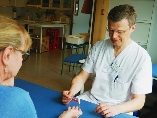 Anders Björkman, klädd i vita sjukhuskläder sitter vid ett bord. Mitt emot honom sitter en kvinna. Hon har lagt sin hand på bordet med handflatan uppåt. Anders Björkman vidrör hennes fingertoppar med en nål.