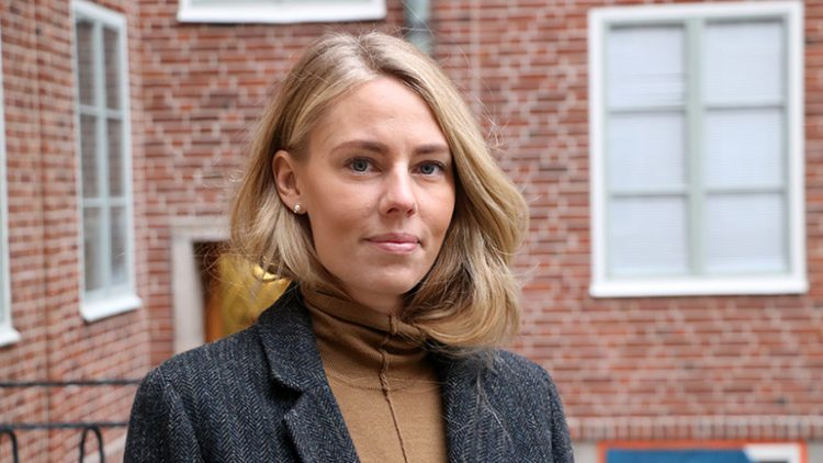 Bilden är en porträttbild av Anna Klinge. Hon står ute och bakom henne syns en röd tegelbyggnad.