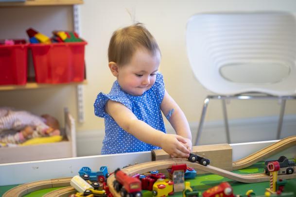 På bilden ses ett litet barn i blå klänning med vita prickar. Barnen leker med ett briotåg som finns i lekrummet