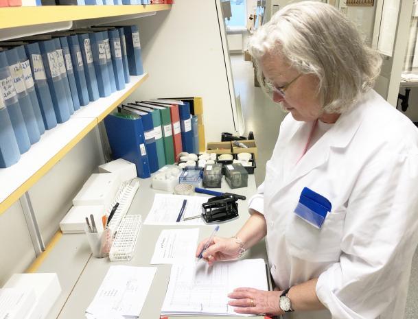 Carina Törn är klädd i vit labbrock. Hon står vid en labbänk på vilken det står pärmar, provrörsställ och en del papper. Hon ser ut att fylla i ett labbprotokoll