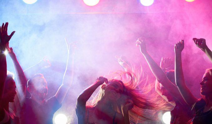Ungdomar som dansar på en klubb. I bildens mitt ses en ung kvinna med lång hår. I bakgrunden flera andra personer som dansar. Allt ses i lilafärgat nattklubbsljus