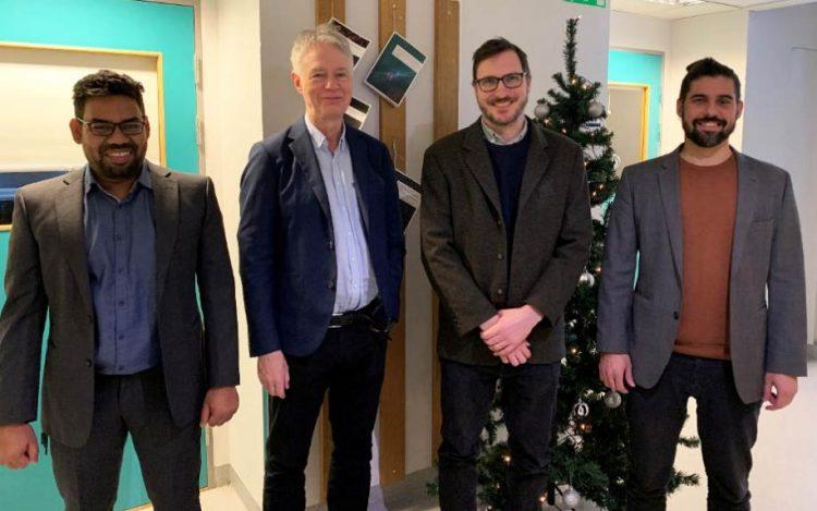 på bilden ses Jens Schoenborg omgiven av sina tre doktorander. De står framför en vägg där man har spikat upp flera avhandlingar. I bakgrunden syns även en julgran.