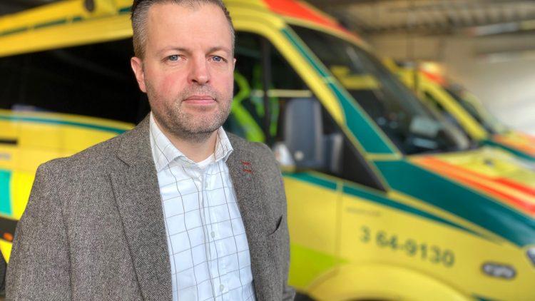På bilden ses Andreas Rantala i halvfigur. Bakom honom syns två ambulanser och det ser ut som att han står inne i en ambulanshall. Andreas Rantala är klädd i en grå kavaj, ljus blårutig skjorta utan slips. Han har kortklippt hår.