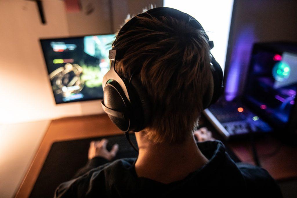 På bilden ser vi vad som ser ut som en ung man med kortklippt hår och hörlurar över öronen. Vi ser honom bakifrån, huvudet och en bit av axlarna och framför honom ser vi en datorskärm. Bilden på skärmen är suddig men det ser ut som ett datorspel. Rummet han sitter i är ganska mörkt, endast upplys av denna och ytterligare en skärm