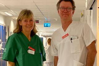 På bilden ses Ingrid Hansen Pupp klädd i en grön sjukhusskjorta. Till höger om henne står David Ley, iklädd vit sjukhusskjorta