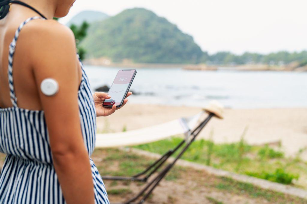 På bilden ses en kvinna snett bakifrån. Det är sommar och hon står på en strand. Hon bär ett linne med smala axelband och man ser att hon på högra överarmen har en så kallad glukossensor. Den ser ut som en vit knapp fastklistrad på armen.