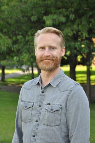 porträttfoto av Anders Pålsson. Han har ljust kortklippt hår och skägg och är klädd i en ljusblå skjorta. Bilden är tagen ute under sommarhalvåret då man ser gröna träd bakom.