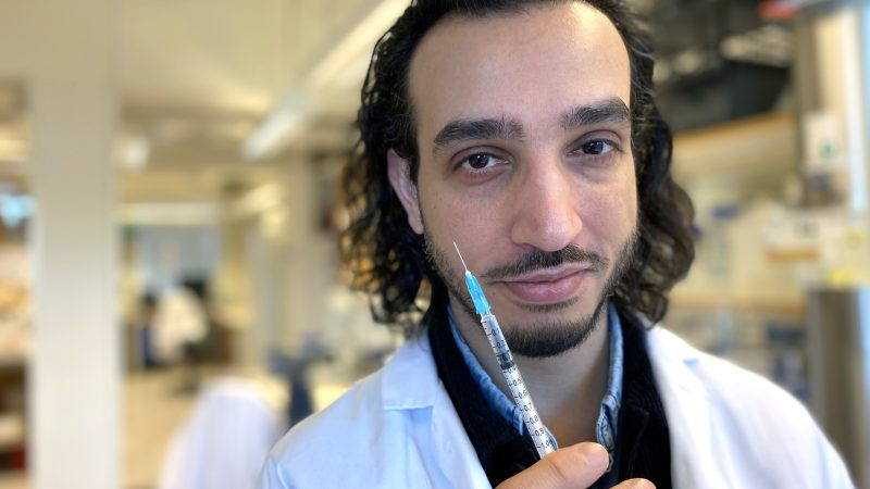 Bilden föreställer Farshid Jalalvand. Han står på labb, har mörkt halvlångt hår. Han har en vit labbrock på sig och håller upp en spruta