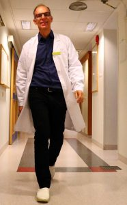 På bilden ses Kristian Riesbeck komma gåendes i en korridor. Han har kort hår och bär glasögon. han är klädd i svarta byxor, mörkblå skjorta och över det bär han en uppknäppt vit labbrock