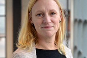 Porträttfoto av Jenny Mattson. Hon har halvlångt ljust hår och är klädd i en svart tröja och ljus kofta