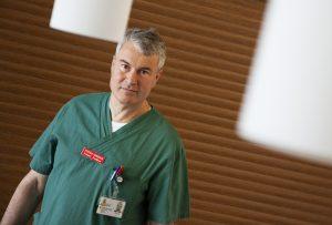 Bild på Stefan Hansson iklädd grön kortärmad sjukhusskjorta. Han har kortklippt gråsprängt hår och tittar rakt in i kameran