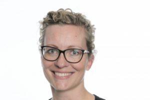 Porträttbild av Marie Jönsson. Hon har kort, ljus, lockigt hår och bär glasögon