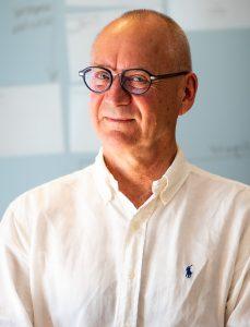 porträttfoto av Leif Dahlberg, klädd i vit skjorta utan slips