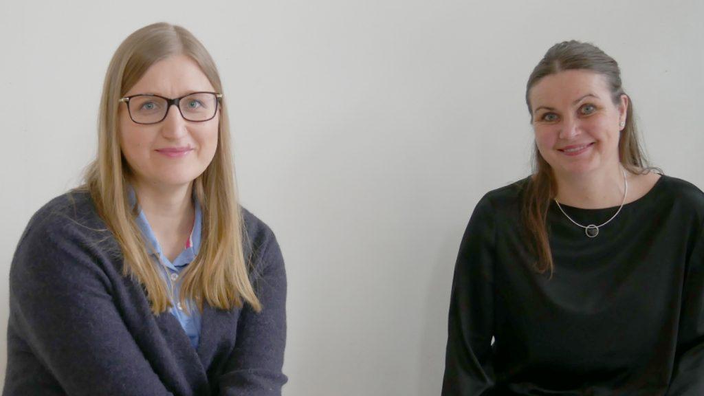 Till vänster på bilden ses Raminta Venskutonytė. Hon har långt blont hår och glasögon. Hon är klädd i en grå kofta. Till höger om henne sitter Karin Lindkvist. Ho är klädd i en svart tröja och har långt brunt hår och Karin Lindkvist.