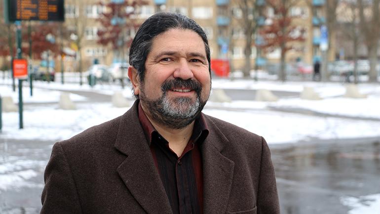 porträttbild på Sasan Naraghi. Han är klädd i mörk skjorta utan slips och en brun kavaj. Han har mörkt lite gråsprängt hår som ser ut att vara samlat i en hästsvans. Han har kortklippt gråsprängt helskägg.