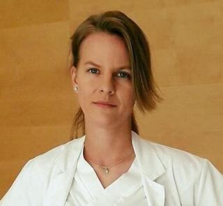 porträttbild av Madeleine Johansson. Hon har ljusbrunt hår uppsatt i en hästsvans och man ser att hon är klädd i vita sjukhuskläder