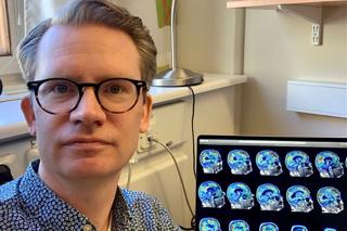 porträttbild av Ruben Smith. Till höger snett bakom honom ses hans datorskärm med bilder av hjärnavbildningar
