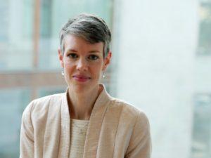 Porträttbild av Johanna Säll Sernevi. Hon har kortklippt lite gråsprängt hår och är klädd i en ljus kavaj