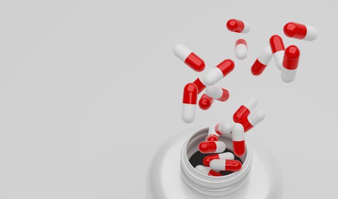 På bilden ses en vit öppen pillerburk ur vilken det flyger upp, alternativt ramlar ner, rödvita medicinkapslar