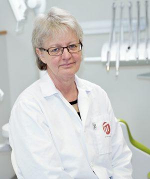 porträttbild på Eva Wolf iklädd vit labbrock. I bakgrundens ser man olika tandläkarinstrument