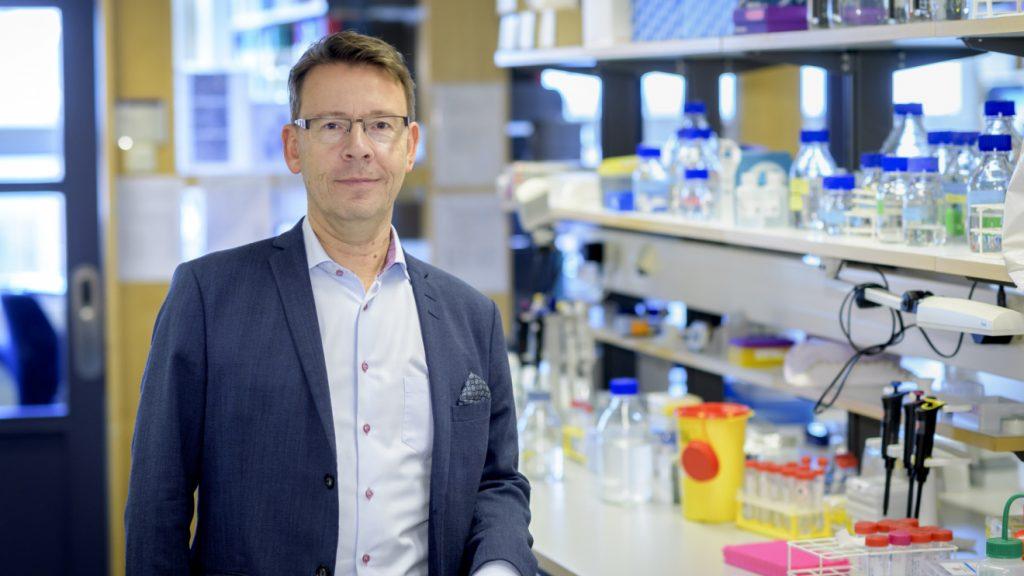 Martin Olsson står på labbet. Bakom honom syns en labbänk och hyllor med glasflaskor på. Han är klädd i en mörkblå kavaj och en ljus skjorta utan lips. han har kort brunt hår och bär glasögon