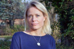 Porträttbild av Kajsa Järvholm. Hon har långt ljust hår som är utsläppt och hon är klädd i en kornblå tröja