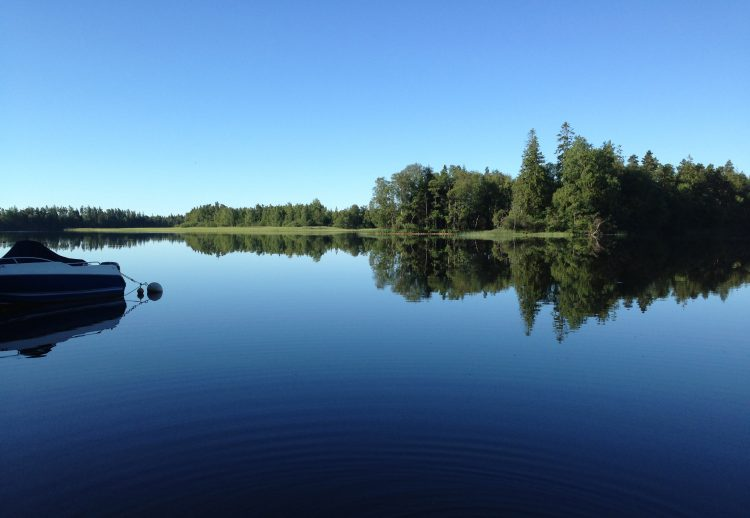 en sommarvy av en sjö med spegelblankt vatten och blå himmel på motsatta stranden ses skog och till vänster i bild ses en ankrad motorbåt