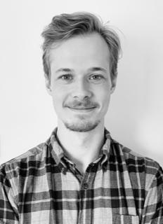 ett svartvitt porträttfoto av Filip Bäckström. Han har mörkblont kortklippt hår, hakskägg, mustasch och är klädd i en rutig skjorta