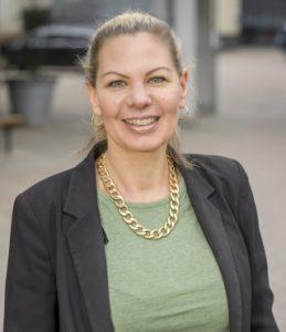 Porträttbild i halvfigur av Gisela Lilja. Hon har långt ljus hår som är uppsatt i en svans. Hon är klädd i en grön tröja och grå kavaj och bär ett halsband i form av en kraftig, guldfärgad kedja.