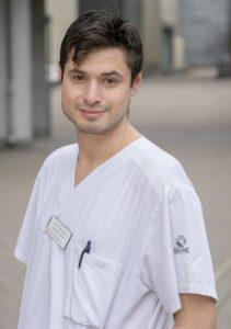 porträttfoto av Josef Dankiewicz i halvfigur. Han är klädd i vit kortärmad sjukhusskjorta med en namnbricka på. Han har mörkbrunt kortklippt hår