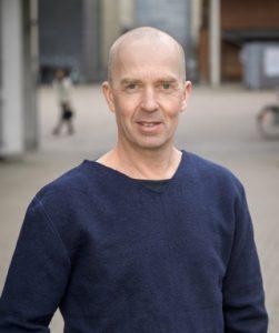 Porträttfoto av Niklas Nielsen. Han är klädd i en blå tröja och har slätrakat huvud.