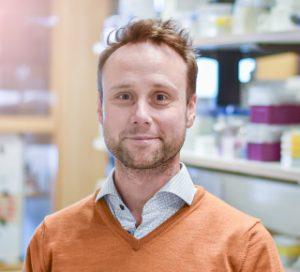 Porträttbild av Sebastian Palmqvist. Han har mörkblont kortklippt hår och ett ljust hakskägg. Bilden är tagen på labbet då man i den suddiga bakgrunden kan ana labbhyllor med flaskor och lådor