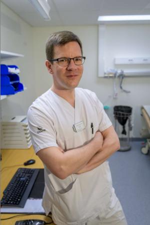 Bild på Andreas Puschmann. Han har kortklippt mörkblont hår och bär glasögon. Han är klädd i vita kortärmade sjukhuskläder och halvsitter på ett skrivbort. Bakom honom ses ett tangentbord