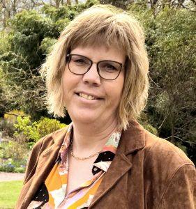 Porträttfoto av Sofi Fristedt. Fotot är taget i en park med blommor och växter i bakgrunden. Sofi Fristedt har halvlångt mörkblont hår och bär glasögon. Hon är klädd i en brun kavaj och blus med olikfärgade fält i gult, vitt, svart och rosa.