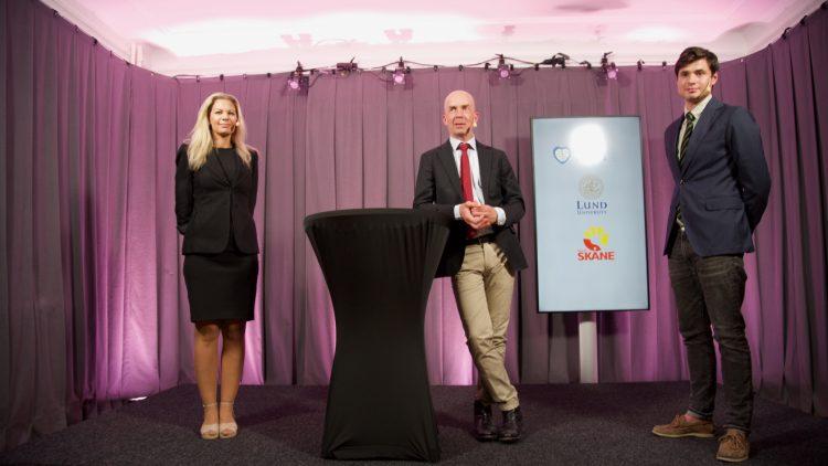 De tre forskarna Gisela Lilja, Niklas Nielsen och Josef Dankiewicz står på en scen i Biskopshuset. Scenen är inramad med ett lila draperi. Alla tre forskarna bär kavaj och Niklas Nielsen lutar sig lätt mot ett högt bord. I bakgrunden ses en tavla med Lunds universitets och Region Skånes loggor