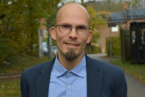 Porträttbild av Tomas Jungert. Han är slätrakad på huvudet och har ett litet hakskägg och bär glasögon. Ha är kädd i blå kavaj och blå skjorta utan slips