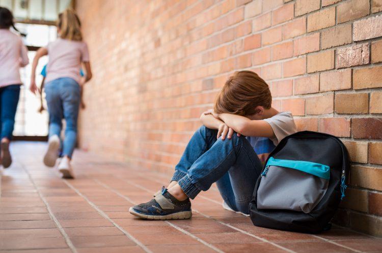 Ett barn i 7-8-års åldern sitter på ett rött klinkergolv och lutar sig mot en röd tegelvägg. Han lutar pannan på sina korsade underarmar som han stödjer mot knäna. Hans kroppshållning signalerar att han är ledsen. Bredvid honom står en mörkblå ryggsäck. I bakgrunden ses flera barn springa därifrån