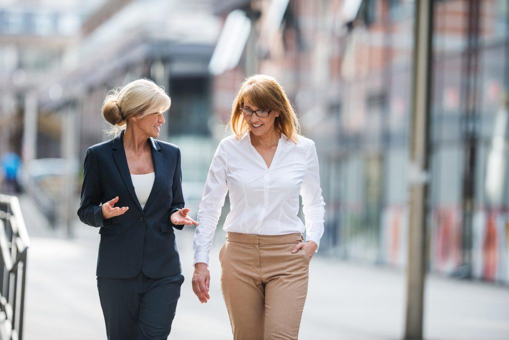 På bilden ses två kvinnor som är inbegripna i ett samtal samtidigt som de promenerar. Den en är klädd i en mörk kavaj och mörka byxor, den andra i beiga byxor och vid skjortblus. Klädseln ger intrycket av att det är ett affärsmöte.