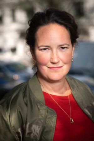 porträttbild av Kajsa Lamm. Hon har mörk uppsatt hår och är klädd i en röd tröja och mossgrön jacka