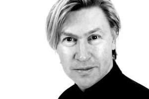 svartvit porträttbild av Sverker Sikström. Han har ljust kort hår med en längre sidolugg. Han är klädd i en svart polotröja