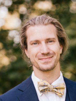 porträttfoto av Tomas Roos. Han har ljusbrunt hår som ser ut att vara långt och hopsatt i en hästsvans. Han har lite skäggstubb och är klädd i en blå kavaj och en ljusgul fluga med mönster på