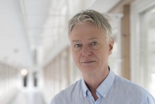 porträttbild av Jens Schouenborg. Han har kort klippt grått hår och bär en ljus skjorta utan slips. Bilden är tagen i en lång ljus korridor och Jens tittar rakt in i kameran. Han bär inte glasögon.