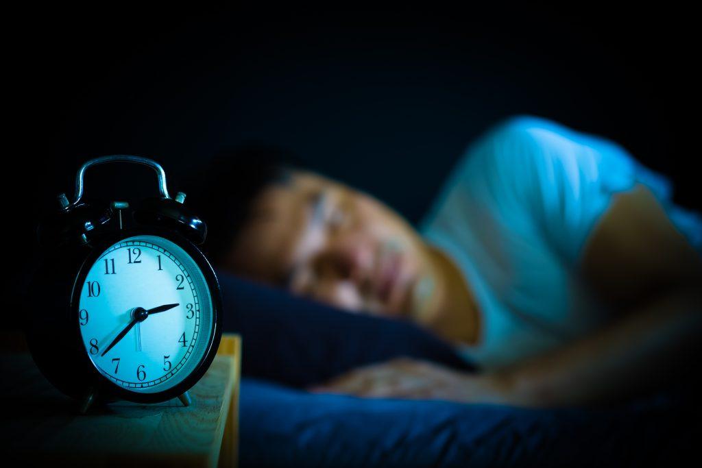 i förgrunden en gammaldags väckarklocka som visar på tjugo i tre. Förmodligen på natten då det är ganska mörkt i bilden och i bakgrunden ses en sovande man