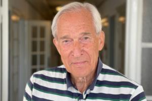 Porträttbild Åke Lernmark. Han har kort gråvitt hår och är solbränd på bilden. Han är klädd i en blåvitrandig t-tröja