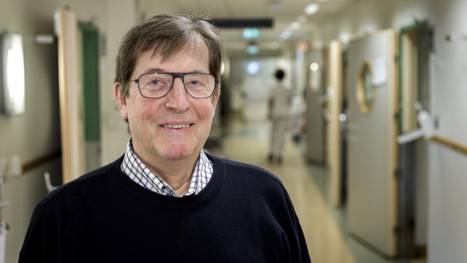 porträtt av äldre man med glasögon i sjukhuskorridor.