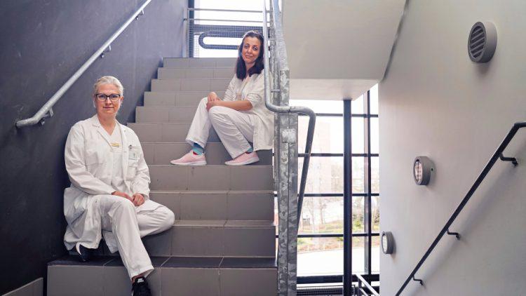 Bilden är tagen i ett trapphus på BMC i Lund. På ett av de nedre trappstegen sitter Åsa Petersén och några trappsteg längre upp sitter Sanaz Gabery. Båda är klädda i vita sjukhuskläder. Åsa har ljust hår och Sanaz är mörkhårig